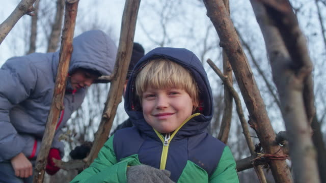 Father building teepee with sons. Riverside in the city