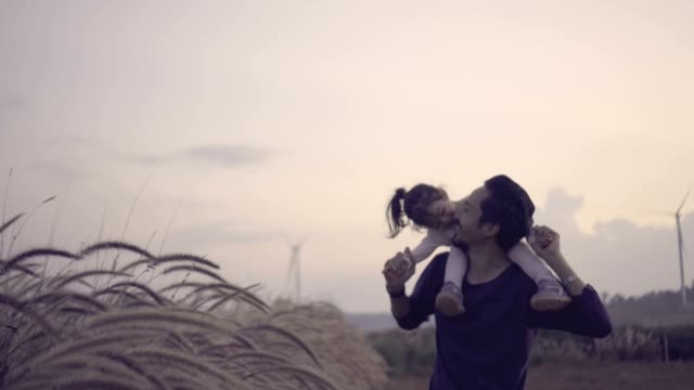 father carries daughter on shoulders and wind turbines on background on holiday - fiducia video stock e b–roll