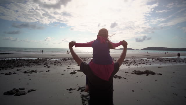 vídeos de stock, filmes e b-roll de slo mo pai carrega filha nos ombros caminhando na praia - dia dos pais
