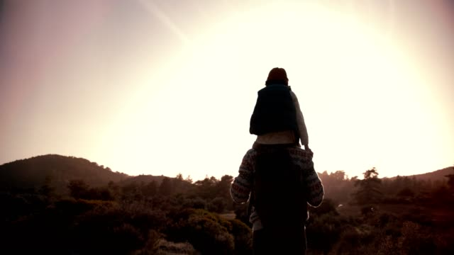 father carrying son on shoulders and hiking on mountain footpath - viaggiare zaino in spalla video stock e b–roll