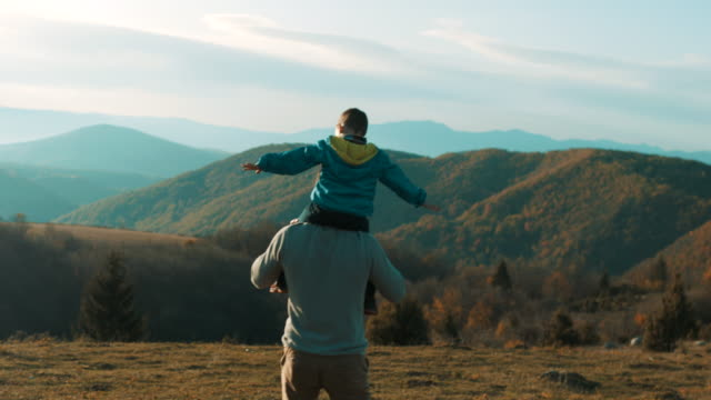 father carrying son on shoulders - trekking video stock e b–roll