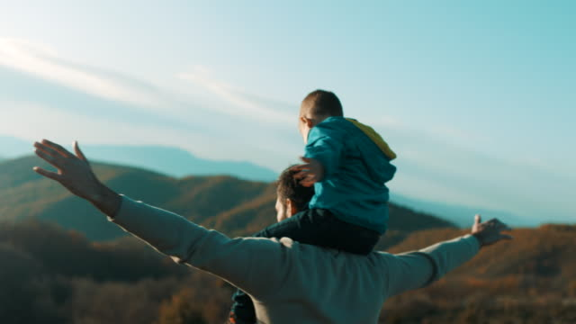Father carrying son on shoulders Father carrying son on shoulders at top of the mountain holiday stock videos & royalty-free footage