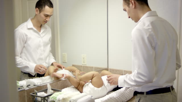 Father changing babies diaper video