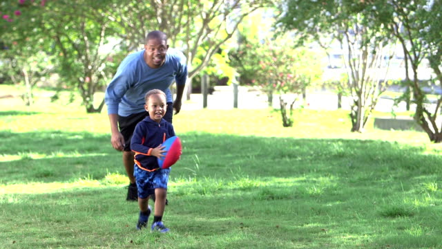 Father chasing little boy carrying football video