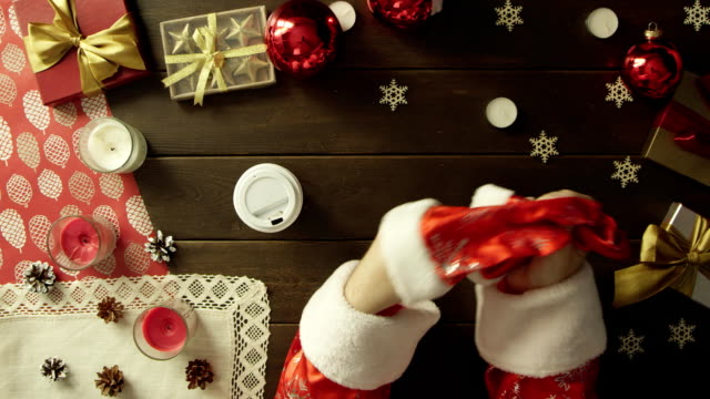 Father Christmas drinks coffee by Christmas wooden table, top down shot video