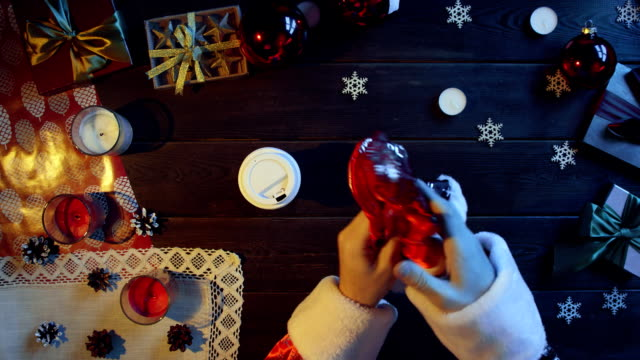 Father Christmas drinks coffee by New Year wooden table, top down shot video