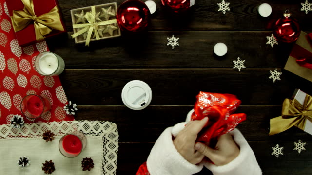Father Christmas drinks coffee by Xmas wooden table, top down shot video