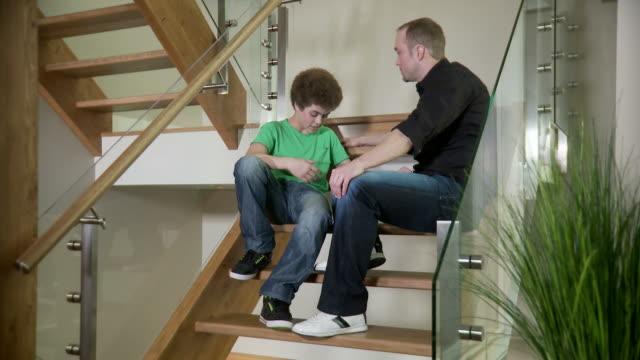 father comforts his son - parent talking to child bildbanksvideor och videomaterial från bakom kulisserna