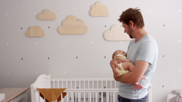 Father Cuddling Sleeping Baby Son In Nursery video