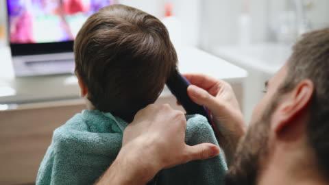 vidéos et rushes de père coupant le cheveu de fils à la maison - coiffure