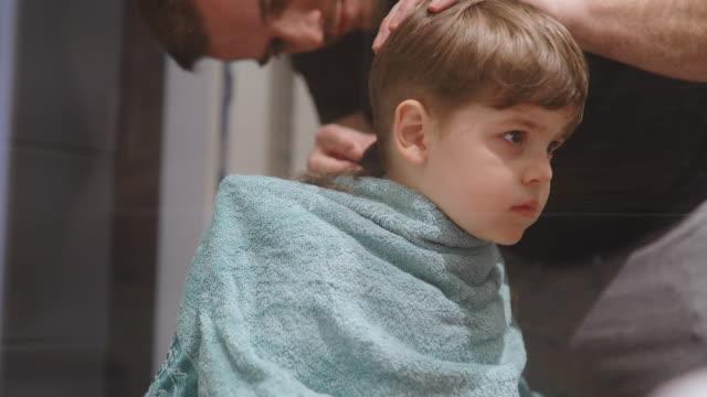 vídeos de stock e filmes b-roll de father cutting son's hair at home - covid hair