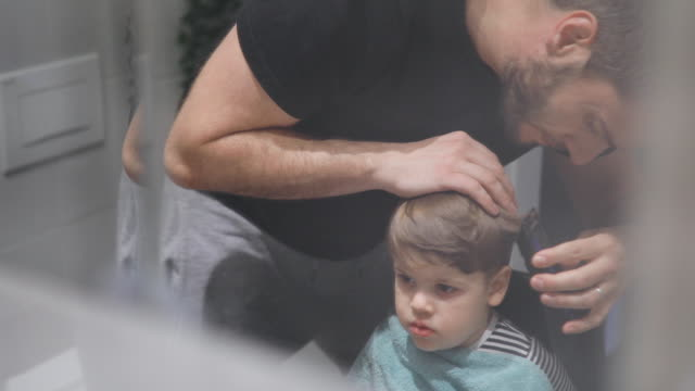 vídeos de stock e filmes b-roll de father cutting son's hair at home - isolado