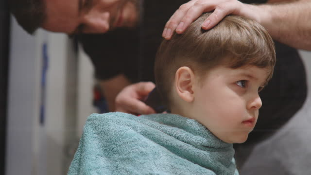 Father cutting son's hair at home Father cutting son's hair at home during the 2020 pandemic lockdown. Covid-19 social distancing hairstyle stock videos & royalty-free footage