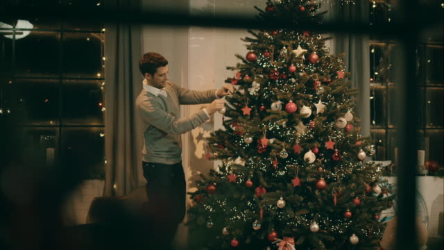 Father decorating christmas tree video