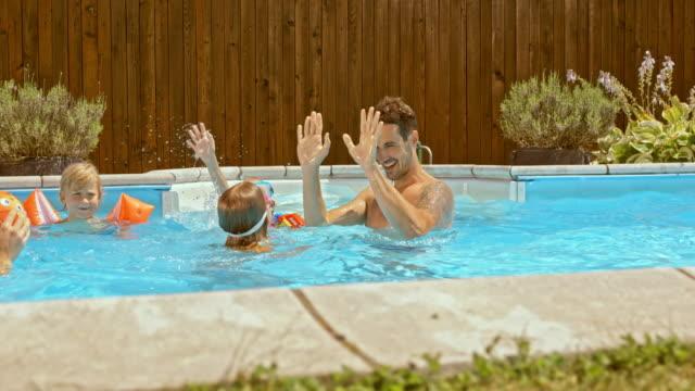 vídeos y material grabado en eventos de stock de cámara lenta padre con hija haciendo alta diez en la piscina - backyard pool