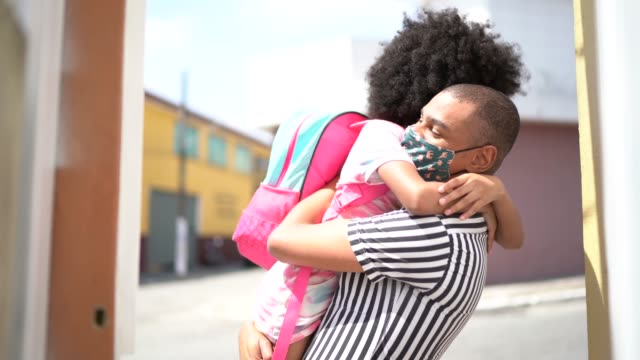 Father embracing before she goes to school using face mask