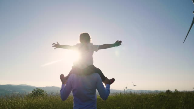 a father engineer, holds his daughter in his arms and runs between the wind turbines with great freedom. - sustainability video stock e b–roll