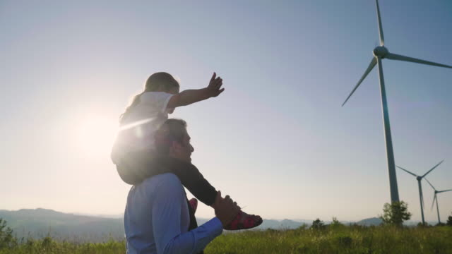 A father engineer, holds his daughter in his arms and runs between the wind turbines with great freedom.