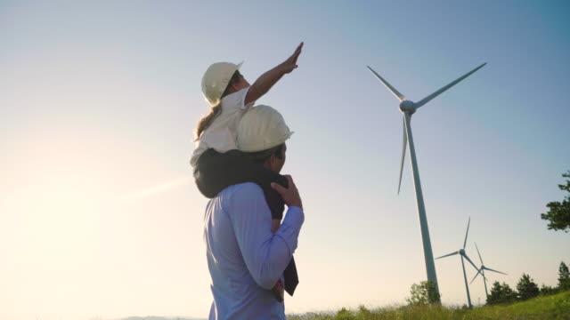 Ein Vater-Ingenieur hält seine Tochter in den Armen und läuft mit großer Freiheit zwischen den Windkraftanlagen. – Video