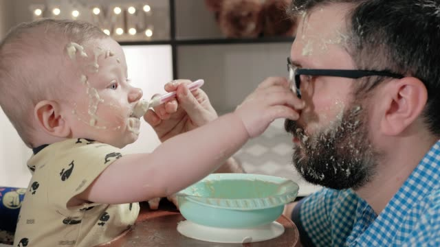 Father feeds baby from spoon. Dad and child have very dirty faces with porridge, baby behaves very messy, often puts his hand on plate and on face of parent. Close-up