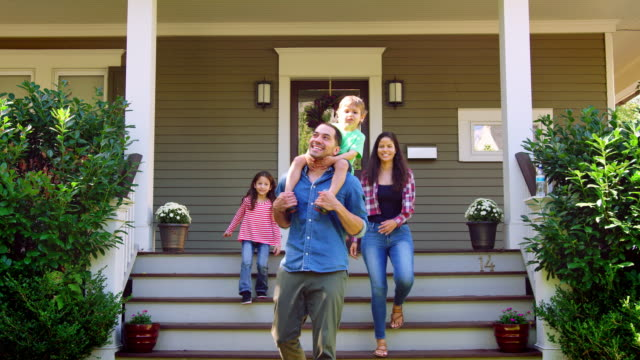 father gives son ride on shoulders as family leave house - family home video stock e b–roll