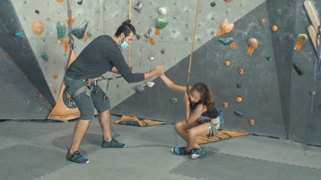 Father giving care and encouragement to his daughter in climbing the wall,Slow motion