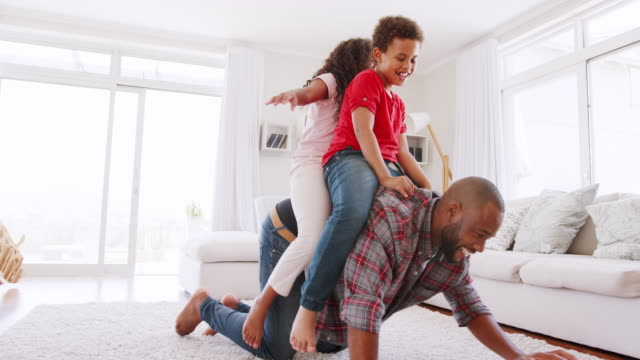 father giving children ride on back in lounge at home - birichinata video stock e b–roll