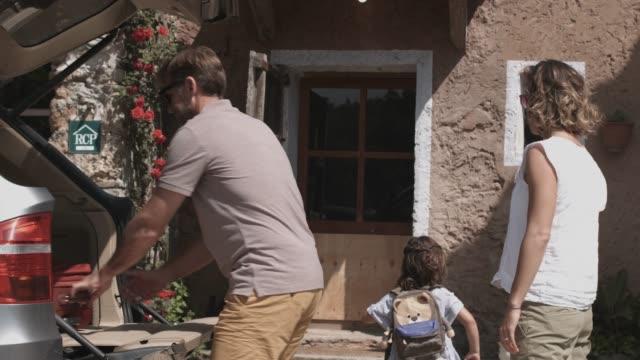 fader som ger bagage till familjen utanför huset - ankomst bildbanksvideor och videomaterial från bakom kulisserna