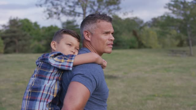 Father giving son a piggy-back ride in a park Caucasian father giving his son a piggy back ride through a park at dusk human back stock videos & royalty-free footage