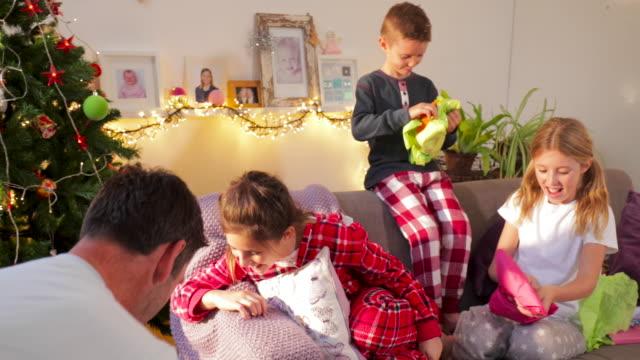 far överlämnar gåvor på juldagens morgon - christmas gift family bildbanksvideor och videomaterial från bakom kulisserna