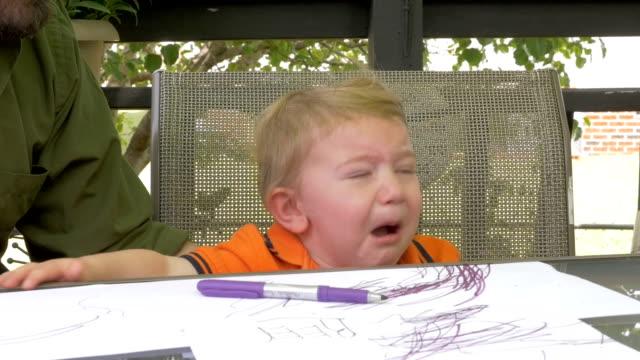 Un padre da un marcador a su hijo de niño frustrado llorando en cámara lenta - vídeo