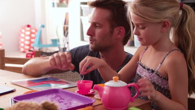 Padre con hija de disponer de tetera y juguetes en el dormitorio - vídeo