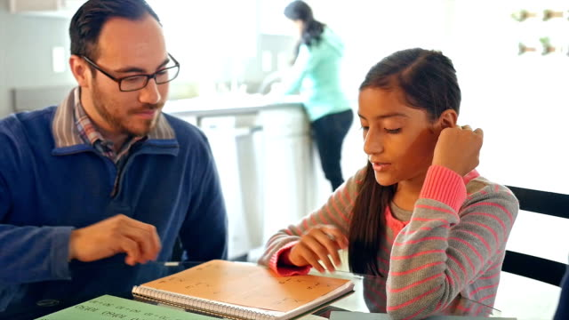 Father helping adolescent daughter with math assignment while homeschooling video