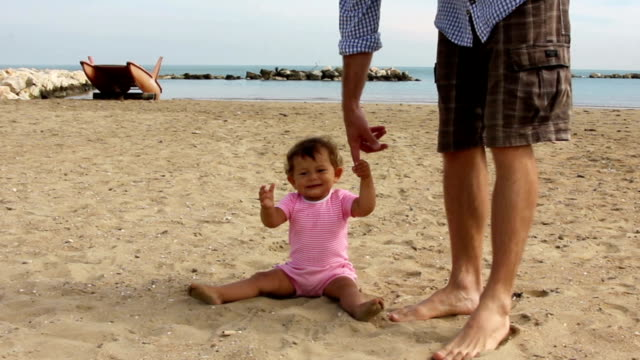 Father helping baby to make first steps video