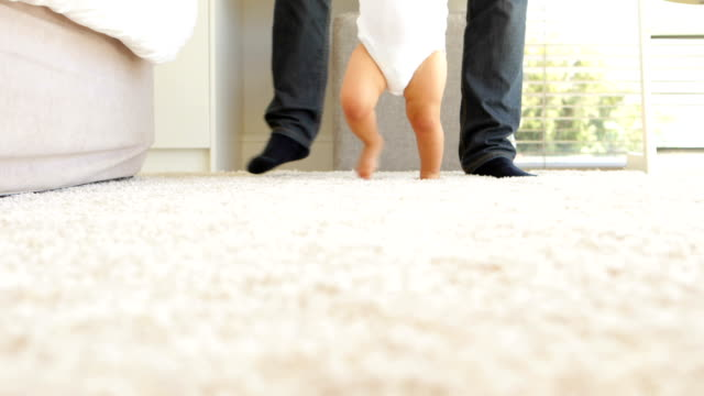 Father helping baby to walk across rug video