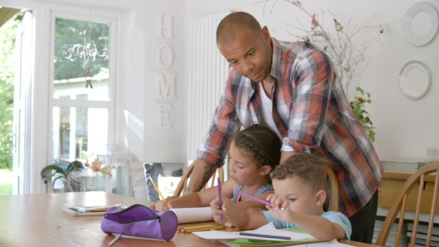 Father Helping Children With Homework At Table video