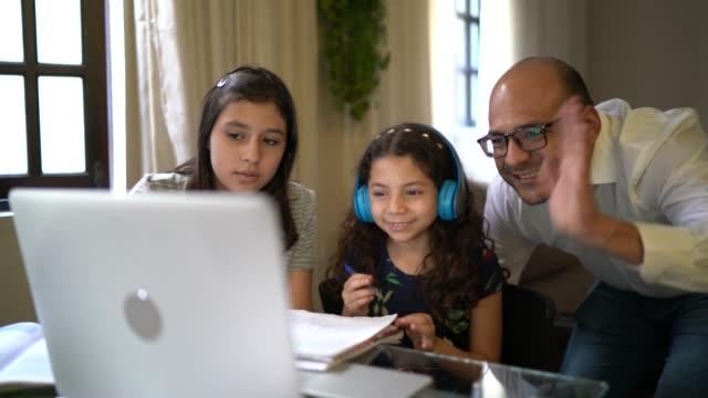 vater hilft tochter bei ihren hausaufgaben auf video-chat e-learning zu hause - nachhilfelehrer stock-videos und b-roll-filmmaterial