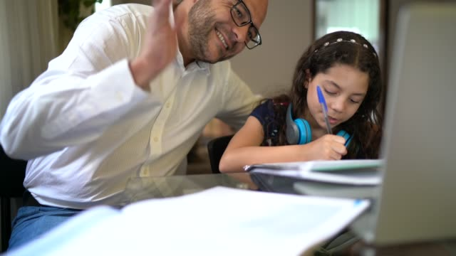 Father helping daughter doing her homework on video chat e-learning at home