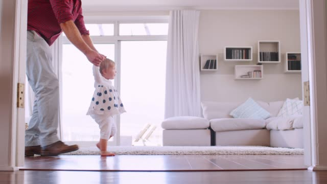 father helping daughter learn to walk at home, side view - edificio residenziale video stock e b–roll