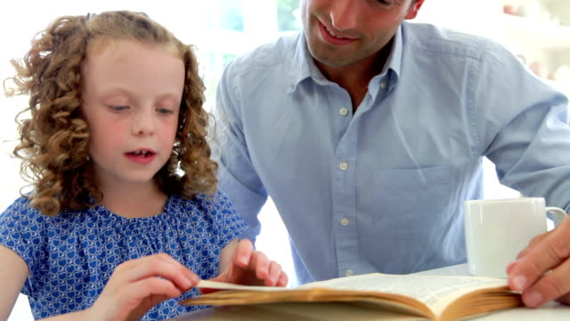 Father Helping Daughter With Homework In Kitchen video