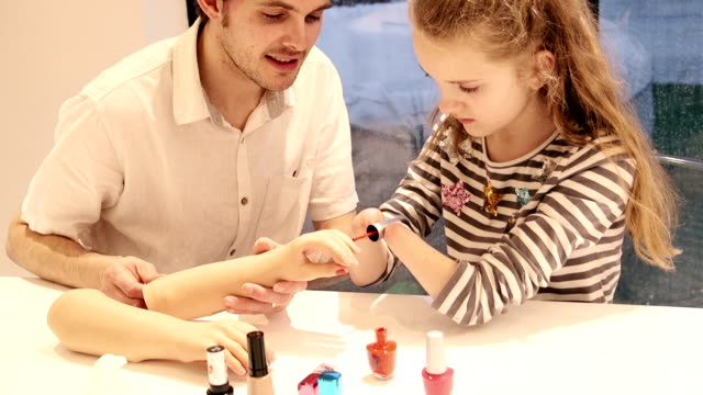 Father Helping his Daughter Paint her Prosthetic Limb Nails A father helping his daughter paint her prosthetic limb nails on the table counter in the dining room, getting rid of all the smudges and mistakes. prosthetic equipment stock videos & royalty-free footage