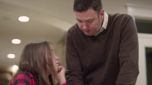 A father helping his daughter with her homework in the kitchen video