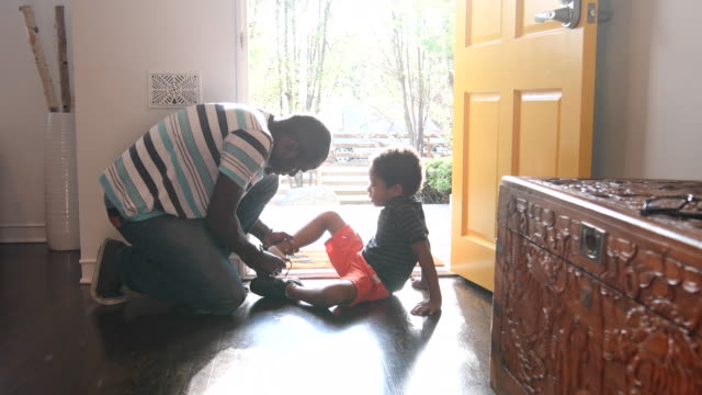 Father helping his son to put shoes on in hallway African American boy is sitting on the floor in sunlight as his father helps him to get his shoes on. love emotion stock videos & royalty-free footage