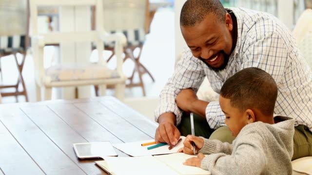 father helping his son with his homework 4k - praca domowa filmów i materiałów b-roll