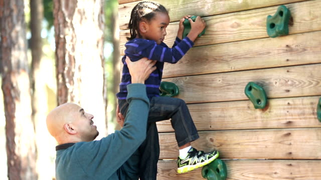 Father helping little boy on climbing wall A father and son playing on a playground. The man, a mature Hispanic man in his 50s, lifts the 4 year old mixed race Hispanic and African-American boy, up onto a climbing wall. outdoor play equipment stock videos & royalty-free footage