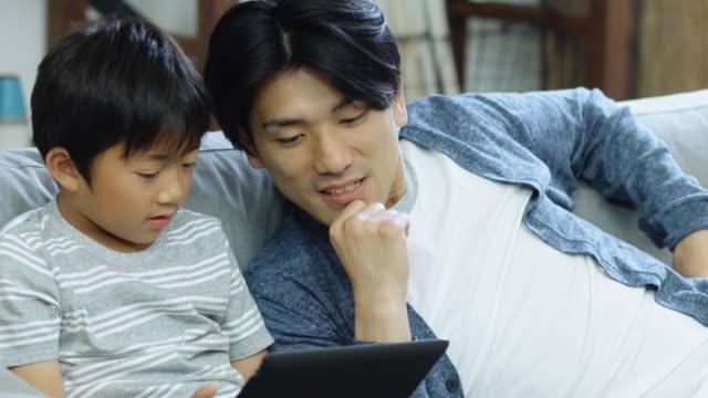 父のコンピューター ゲームをプレイするほとんどの少年を助ける - 男の子点の映像素材/bロール