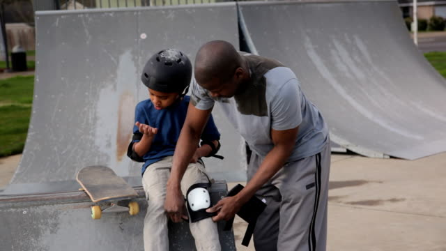Father helping son get skateboard safety gear on video