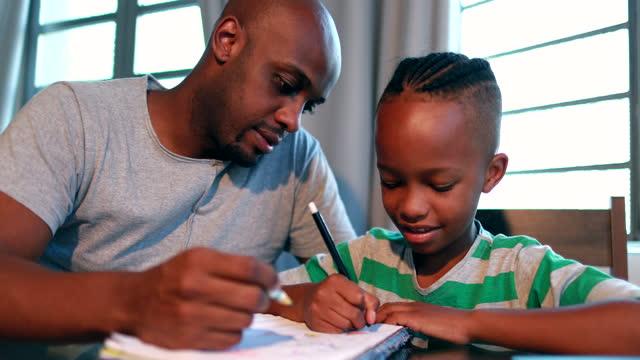 padre che aiuta il figlio con i compiti a casa. papà nero africano che fa da mentore al bambino - padre single video stock e b–roll