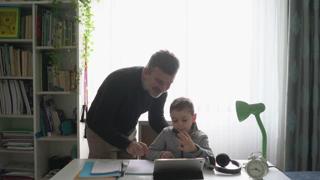 far hjälper son med läxor. - enbarnsfamilj bildbanksvideor och videomaterial från bakom kulisserna