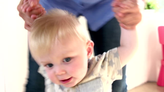 Father Helping Young Son As He Learns To Walk video